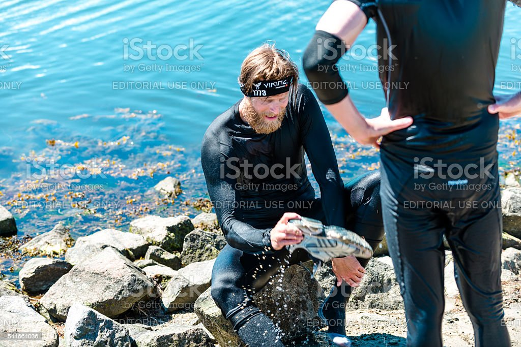 Participant in obstacle course race with wet running shoes stock photo