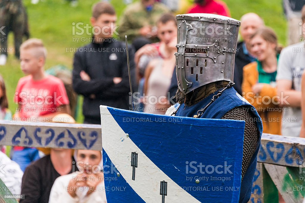 Participant of the festival in knight armor prepares to fights. stock photo