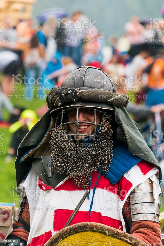 Participant of the festival in knightly armor smiles before the stock photo