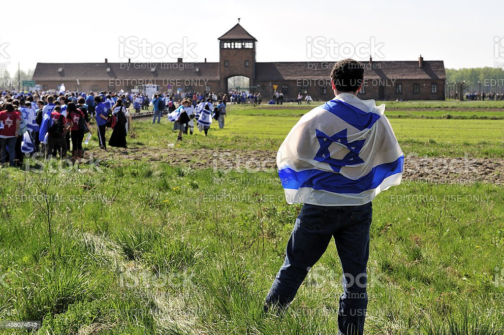Participant wearing an Israeli flag at Auschwitz -Birkenau death camp stock photo