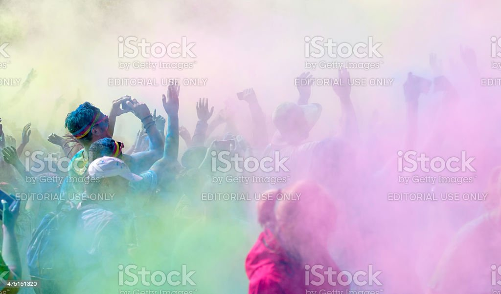 Participants in the Color Run waiving the arms stock photo