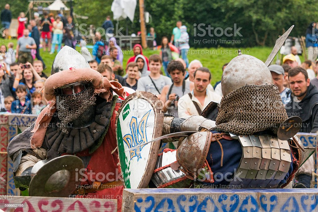 Participants of the festival in knight armor arrange fights stock photo