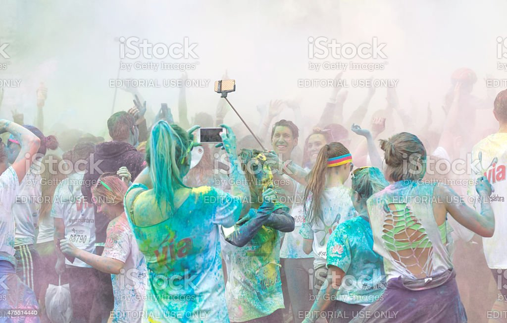 Participator in the Color Run waiving arms in the sky stock photo