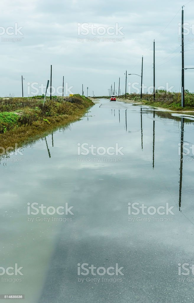 Partly flooded road to public beach stock photo