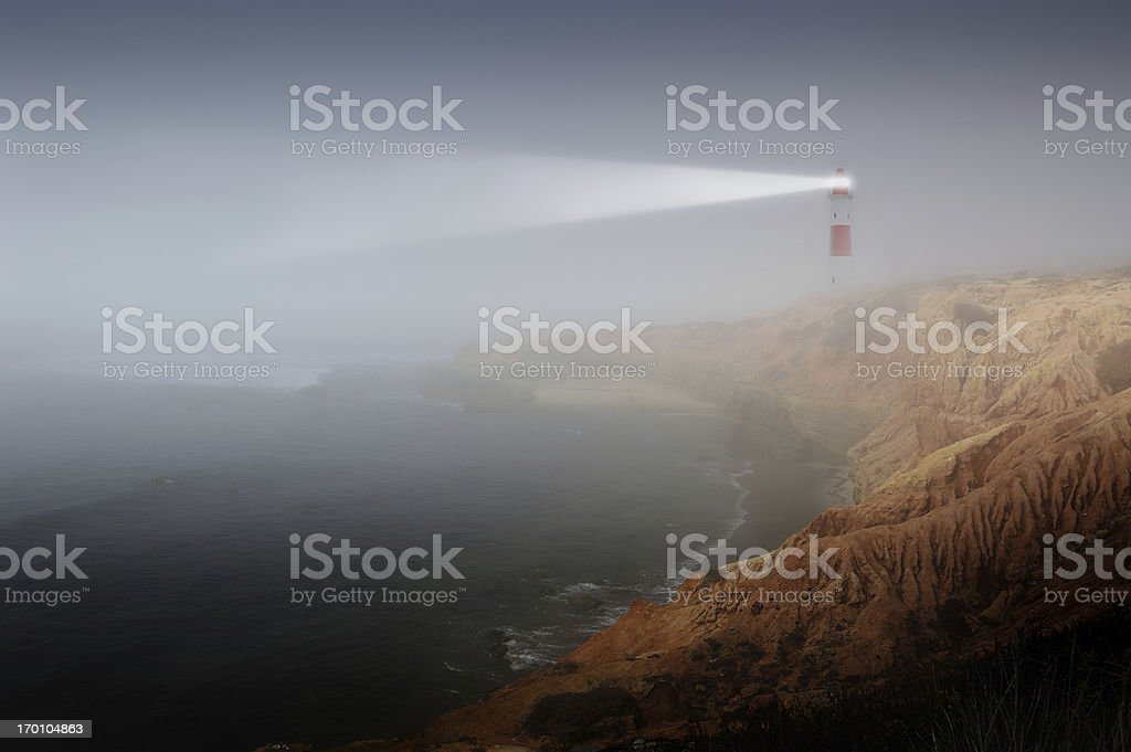 Partly sunlit rock with lighthouse royalty-free stock photo