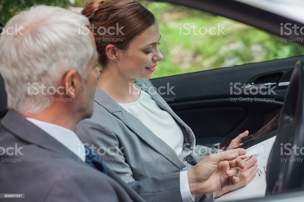 Partners working together in classy car stock photo