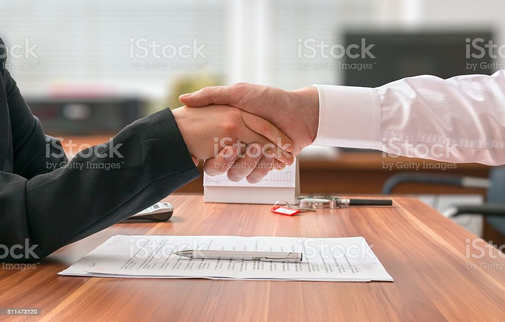 Partnership concept. Businessman and woman sitting shaking hands stock photo