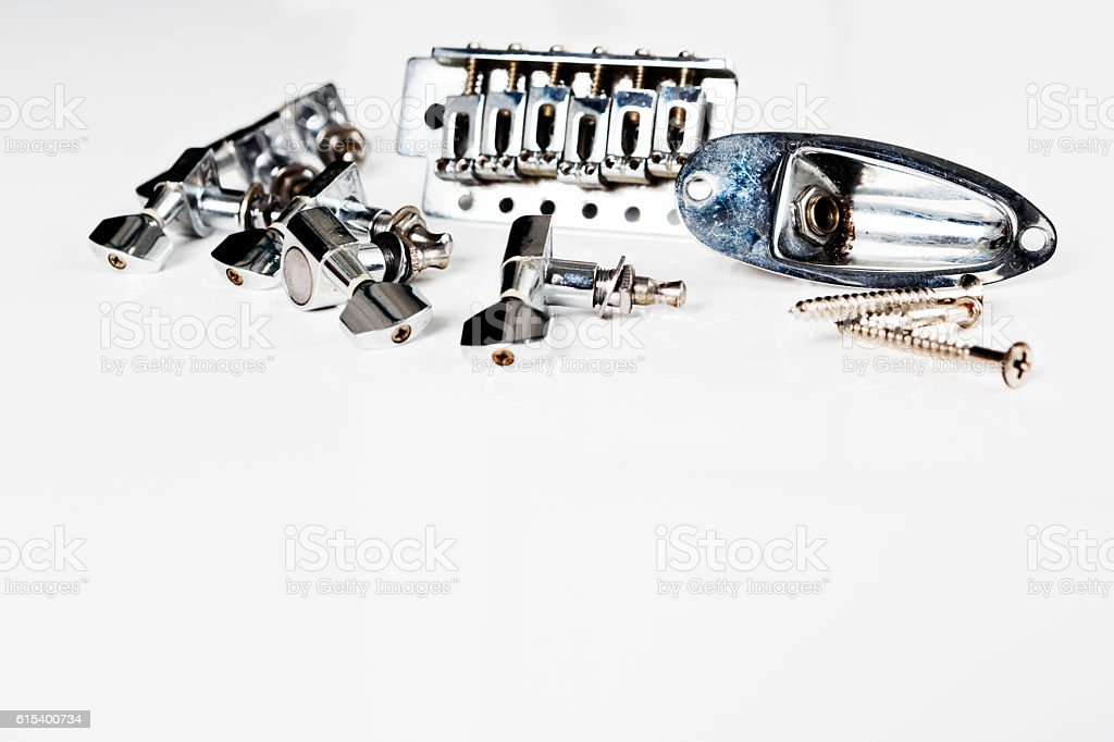 Parts of a broken or dismantled electric guitar on white stock photo