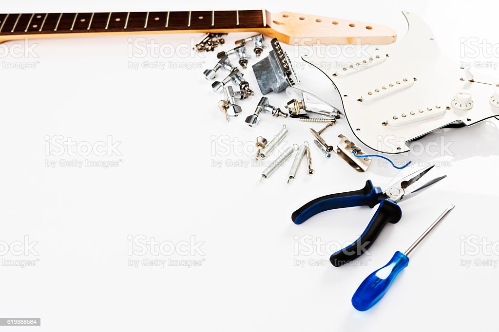 Parts of electric guitar lined up with tools awaiting assembly stock photo
