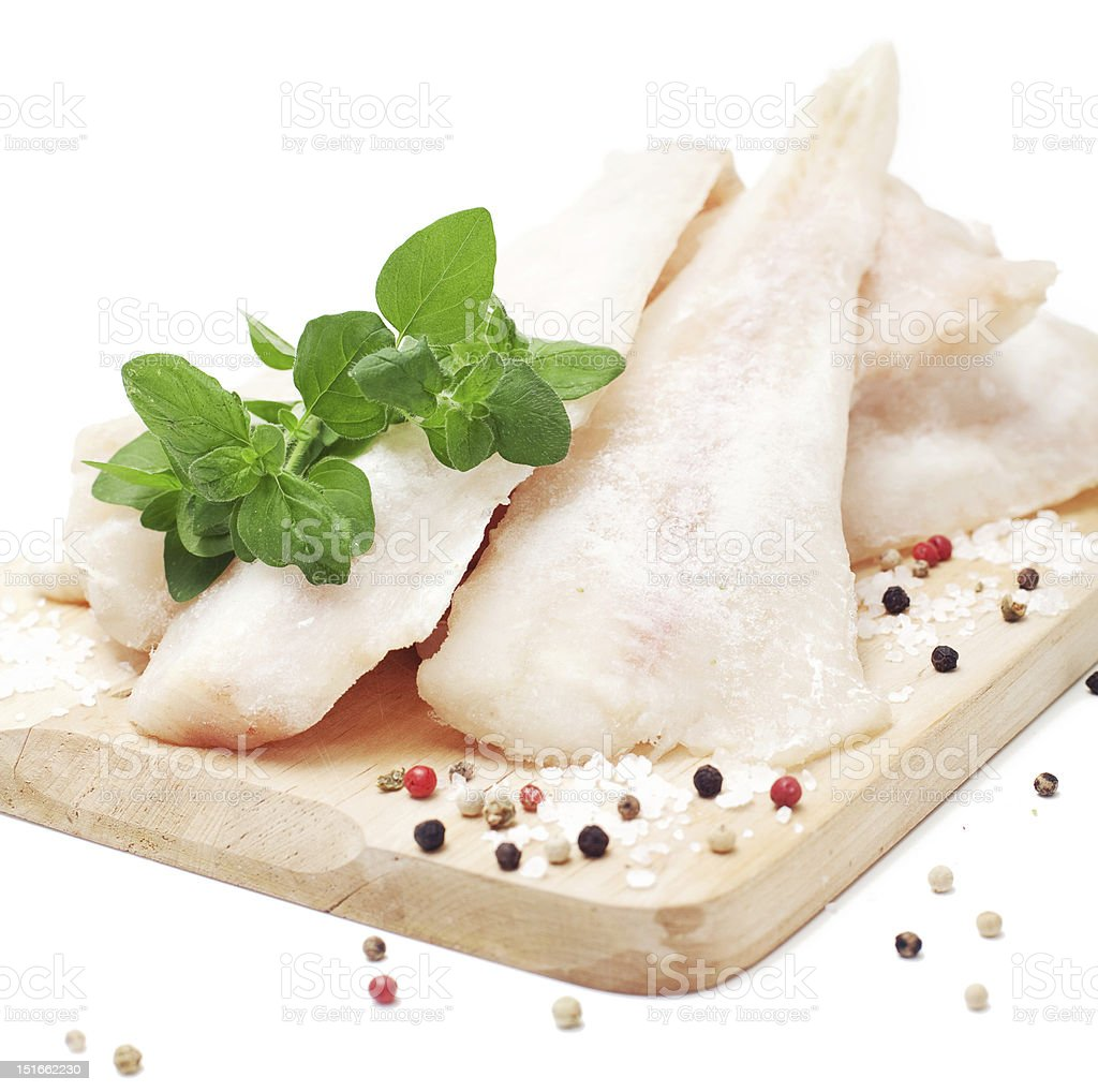 Parts of pollock and seasoning on a wooden board royalty-free stock photo