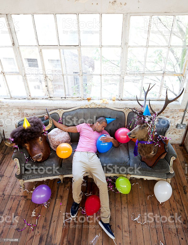 Party animals passed out on couch after a big night stock photo