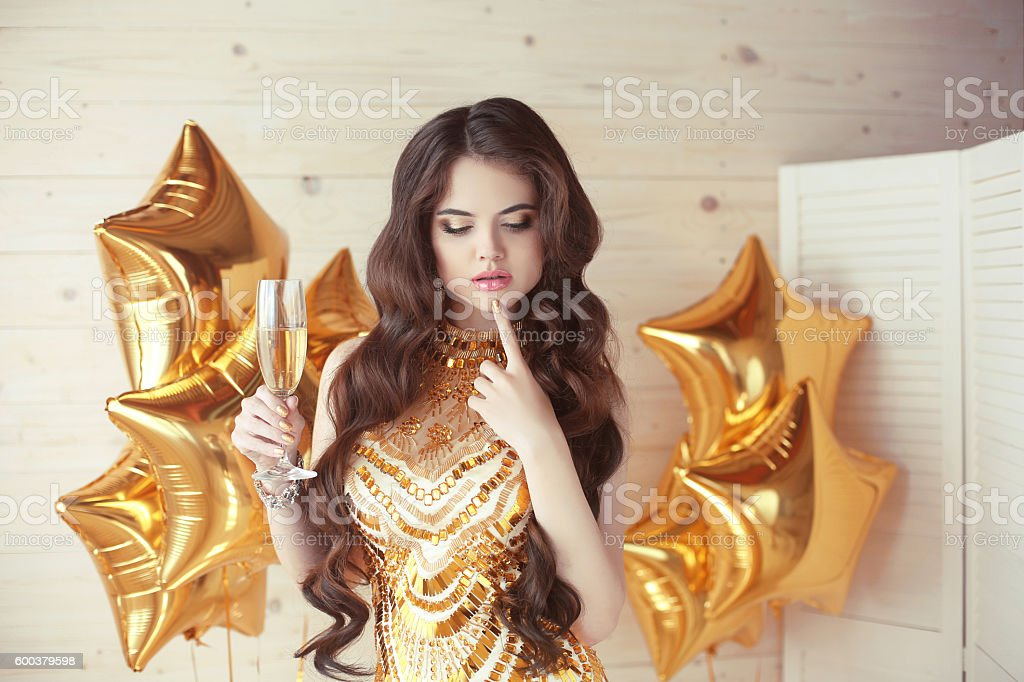 party celebration, gorgeous young woman in golden dress thinking stock photo