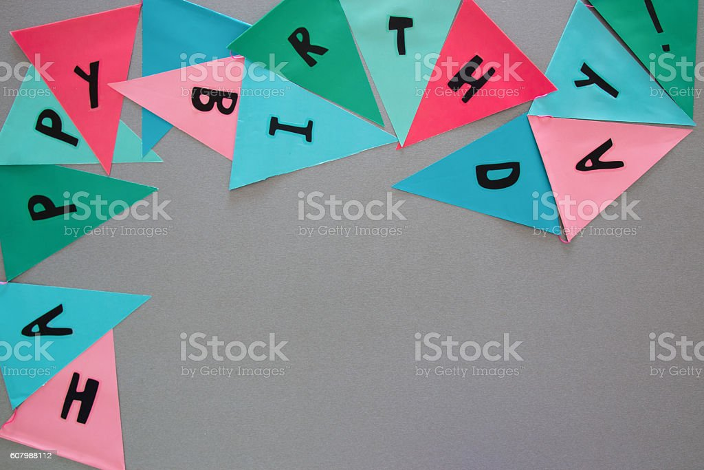 Party colorful flags on grey table with worlds HAPPY BIRTHDAY stock photo