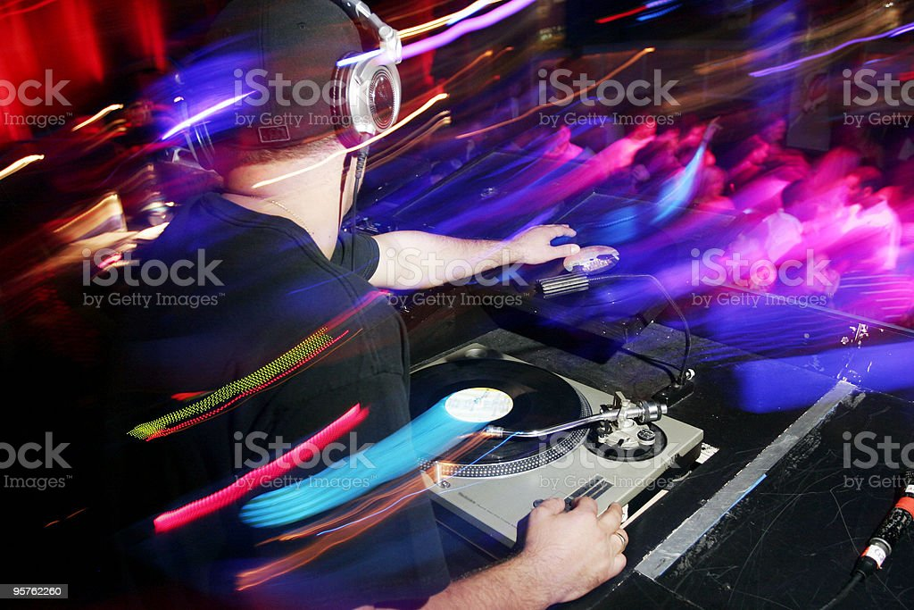 Party DJ in Club with Dancers and Record on Turntable stock photo