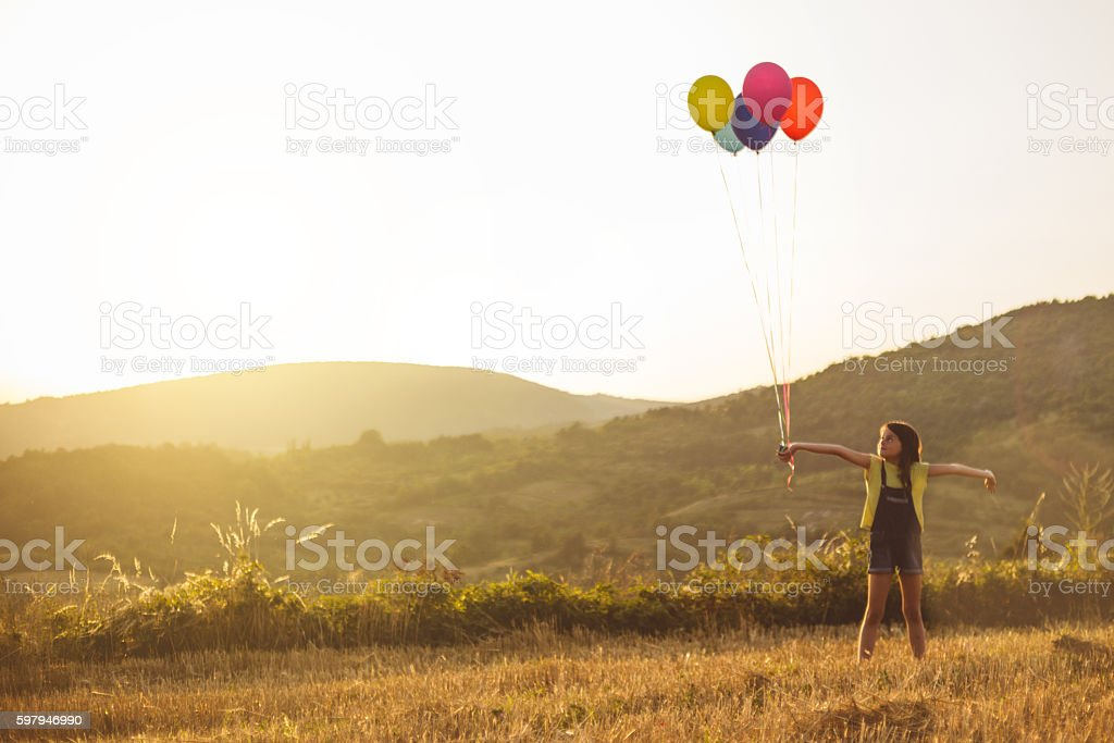 Party girl holding pile of balloons in sunny meadow stock photo