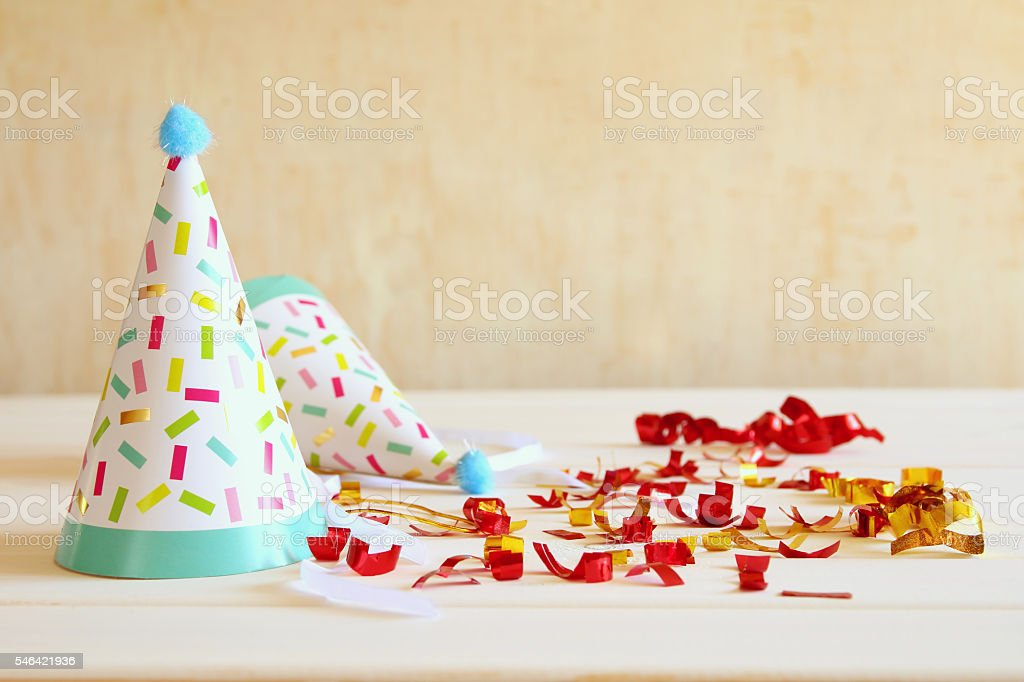 Party hat next to colorful confetti on wooden table stock photo