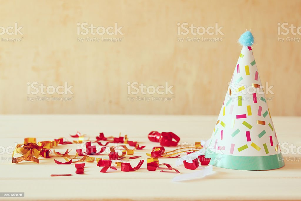 Party hat next to colorful confetti on wooden table. stock photo