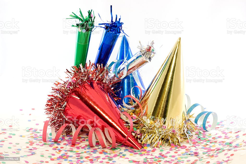 Party hats and confetti sitting on a table stock photo