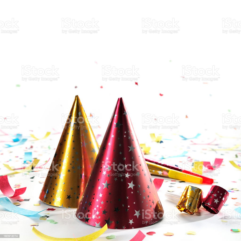Party hats, whistles, horns, confetti isolated on white, studio shot stock photo