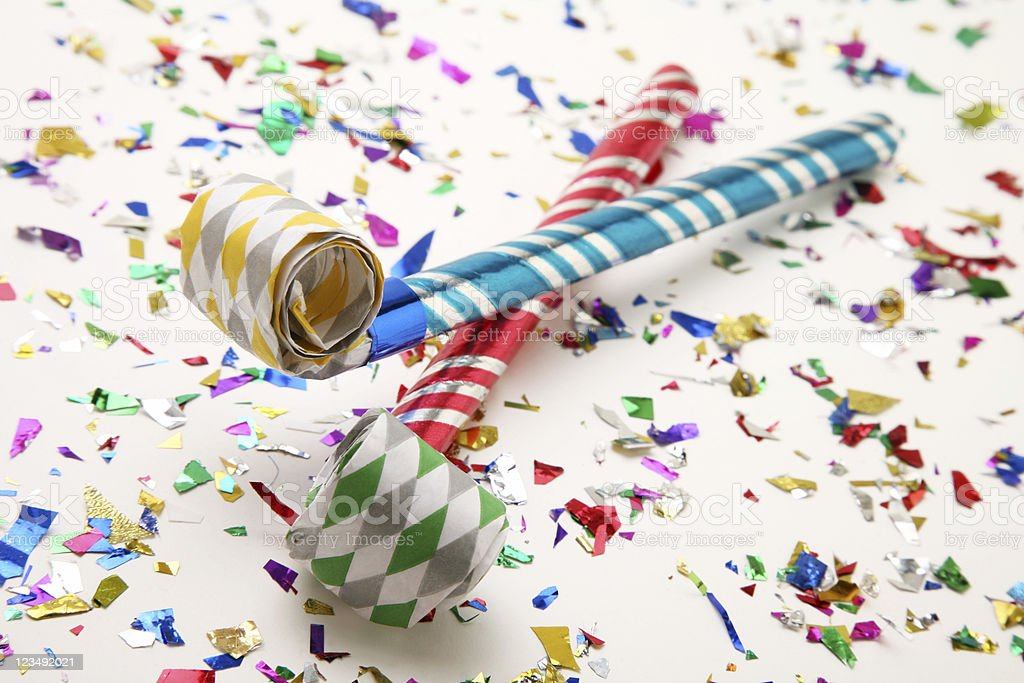 party horn blowers on confetti stock photo