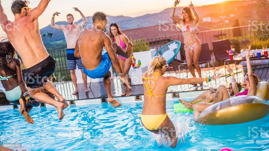 Party people jumping in the pool stock photo