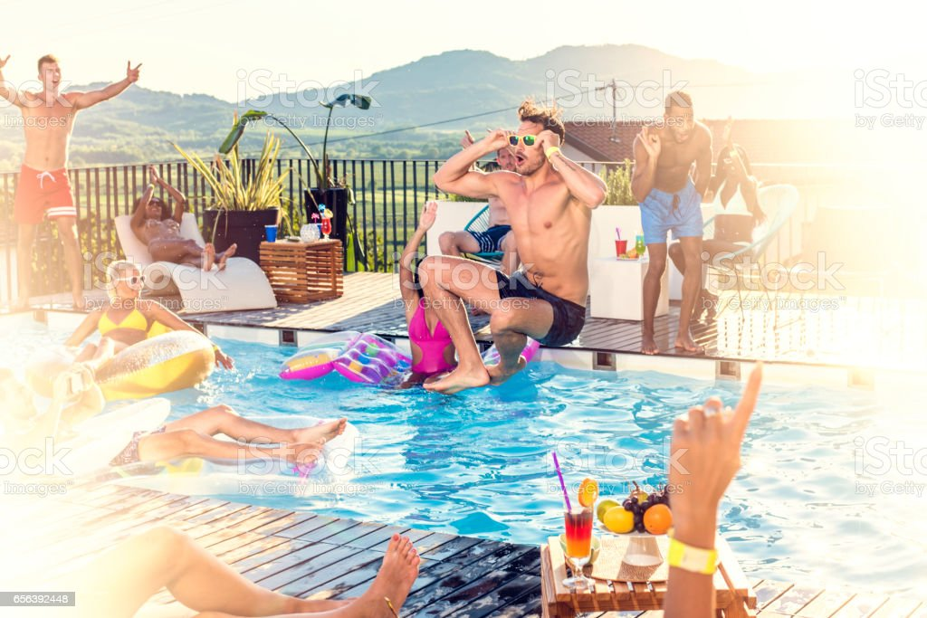 Party people jumping into pool stock photo