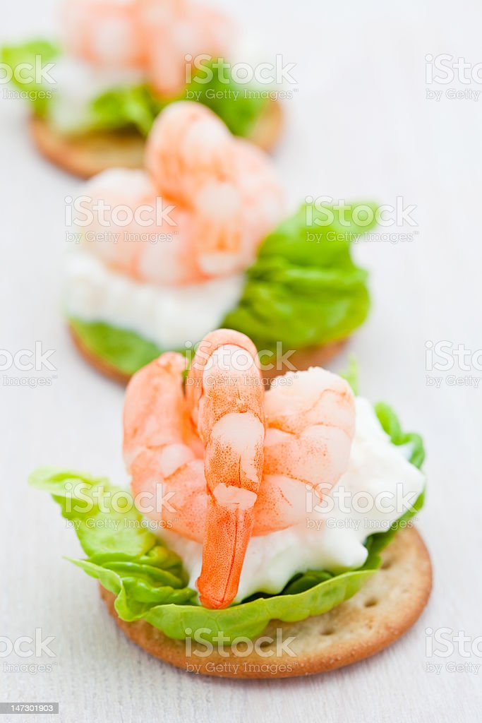 Party snacks. Prawns on a bed of lettuce and cheese royalty-free stock photo