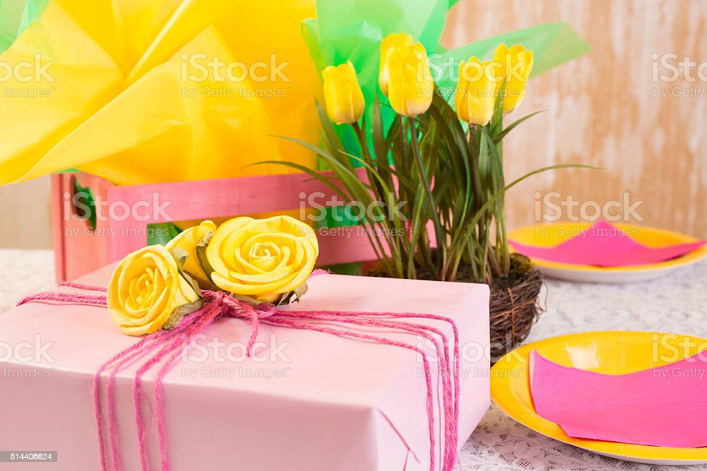 Party time!  Yellow flowers, gifts, plates on dining table.  Feminine. stock photo