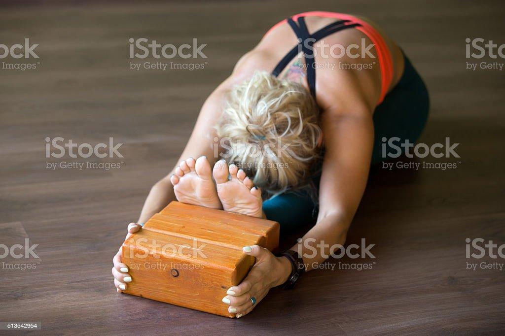 Paschimothanasana posture with Iyengar blocks stock photo