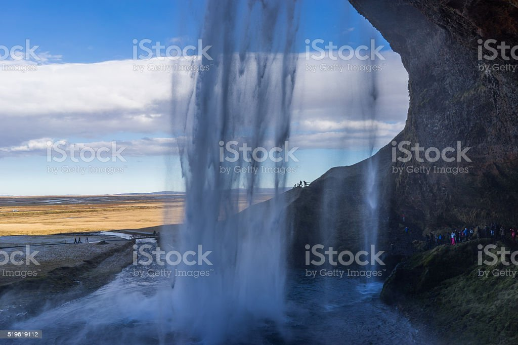 Passage behind a waterfall in the mountains stock photo
