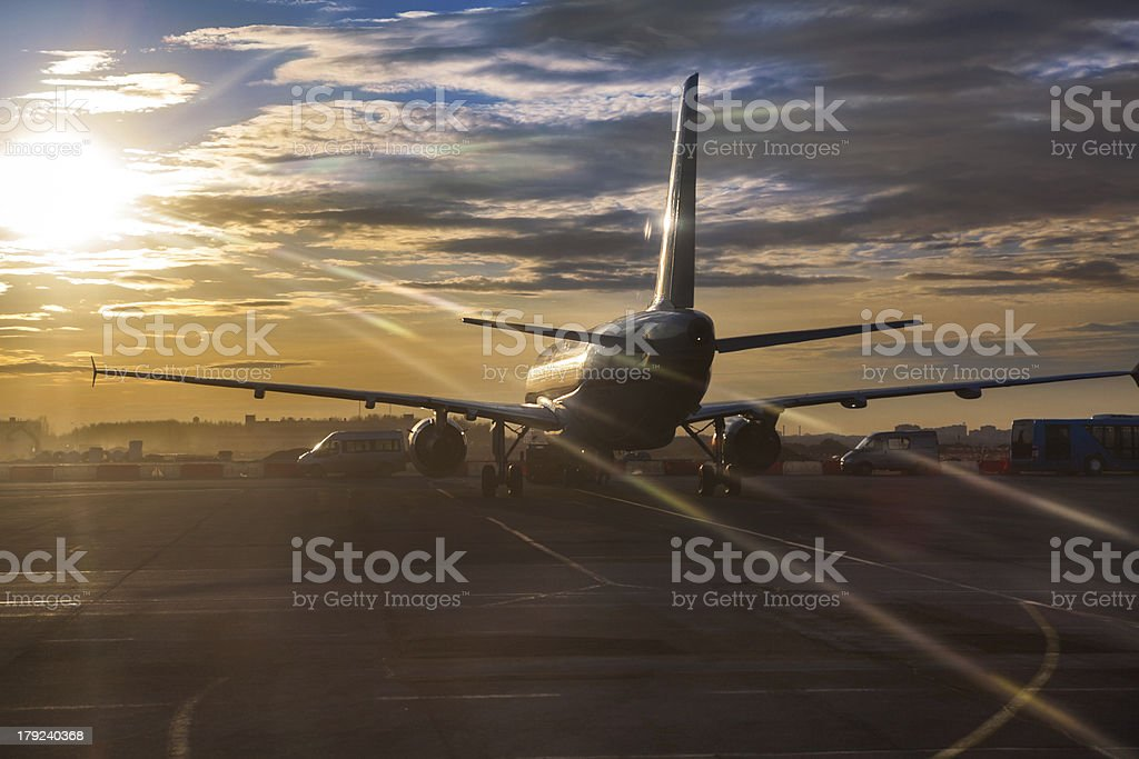 Passenger aircraft riding on runway in sunset sunlights royalty-free stock photo
