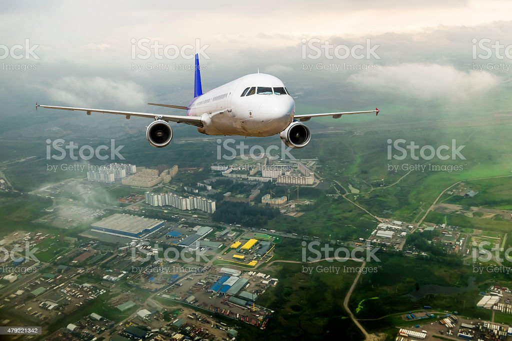 Passenger airliner took off over the roofs of the city stock photo
