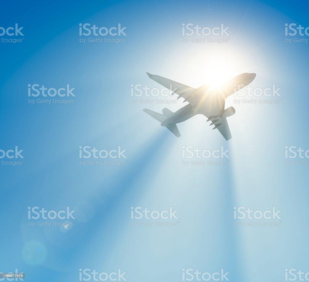 Passenger airplane flying against the sun stock photo