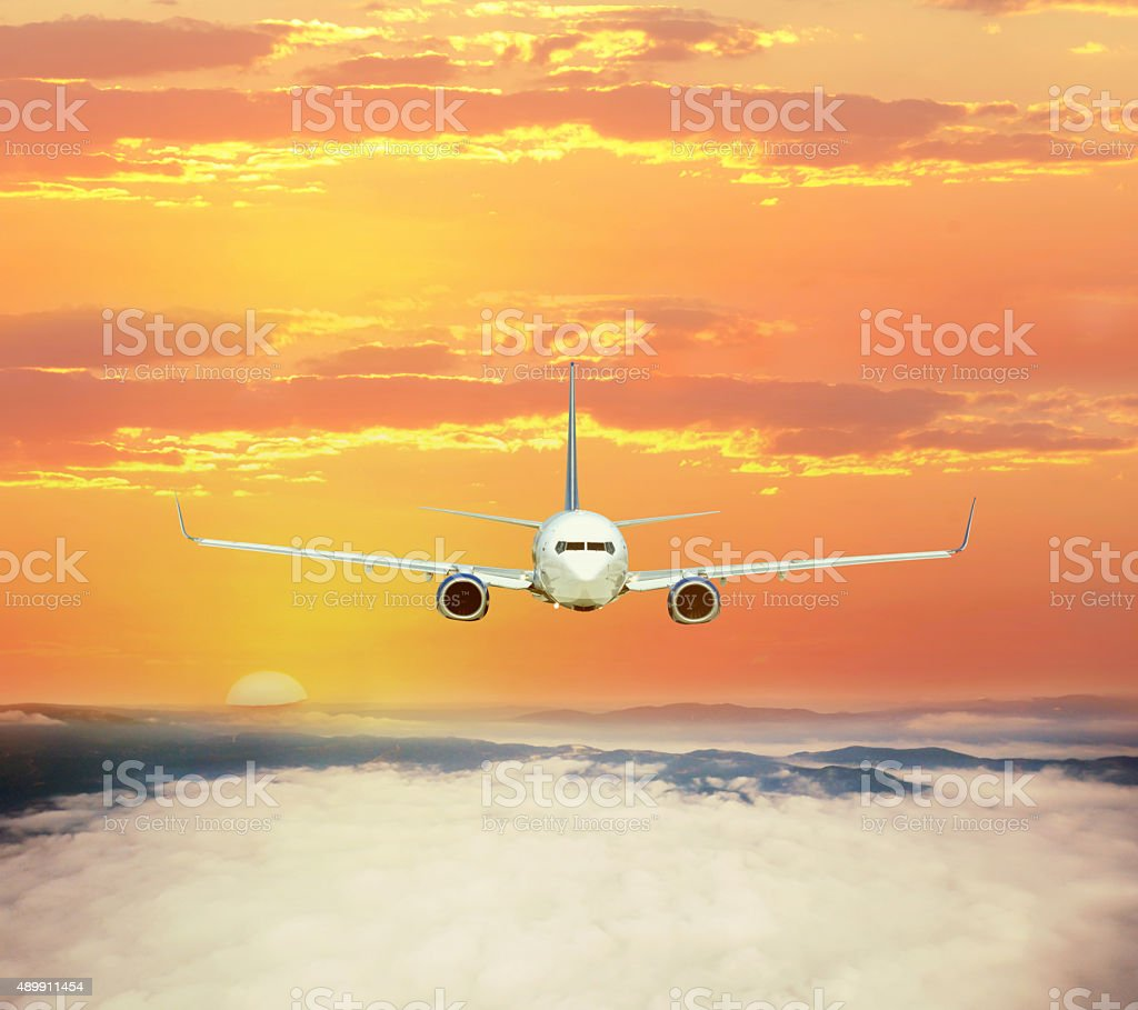 Passenger airplane flying high over the clouds on sunset stock photo