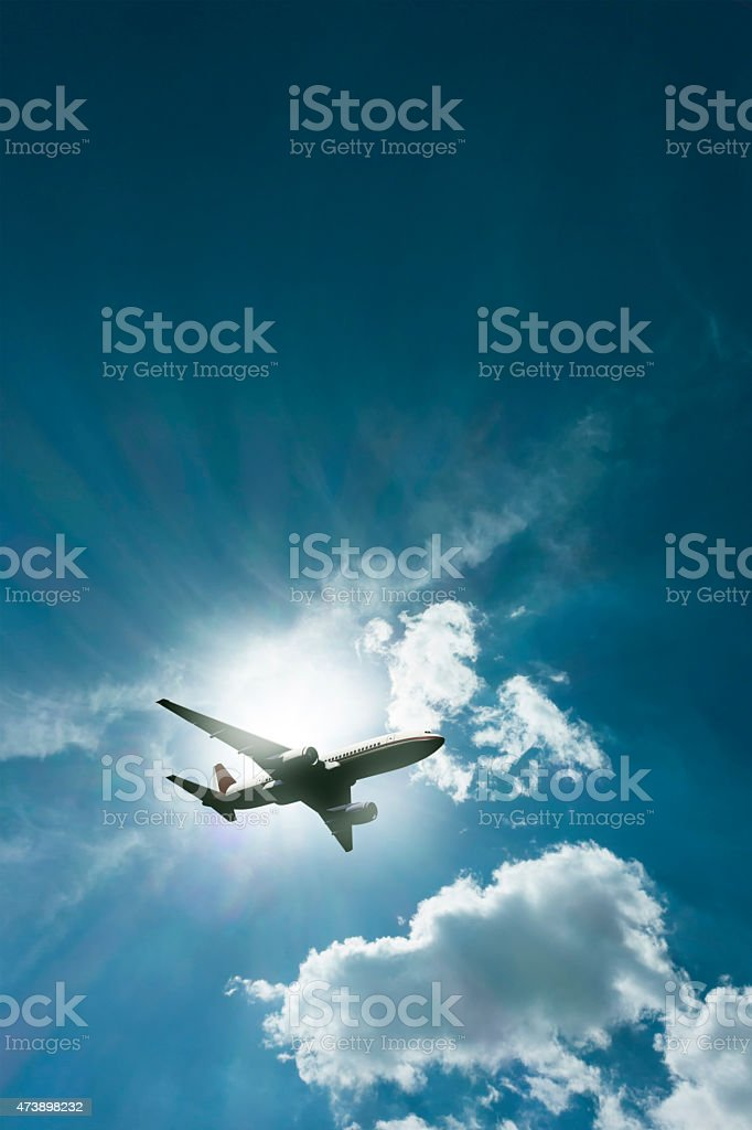 passenger airplane flying into the clouds stock photo