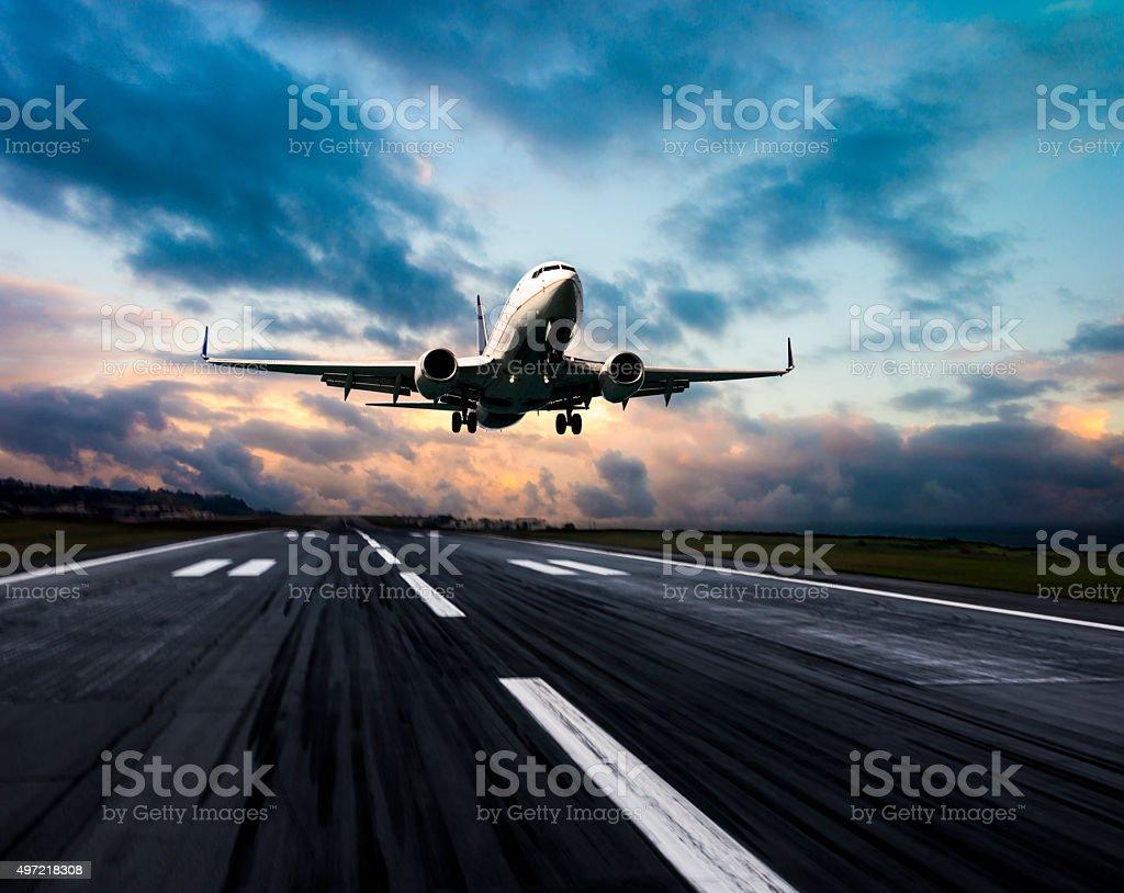 Passenger airplane landing at dusk stock photo