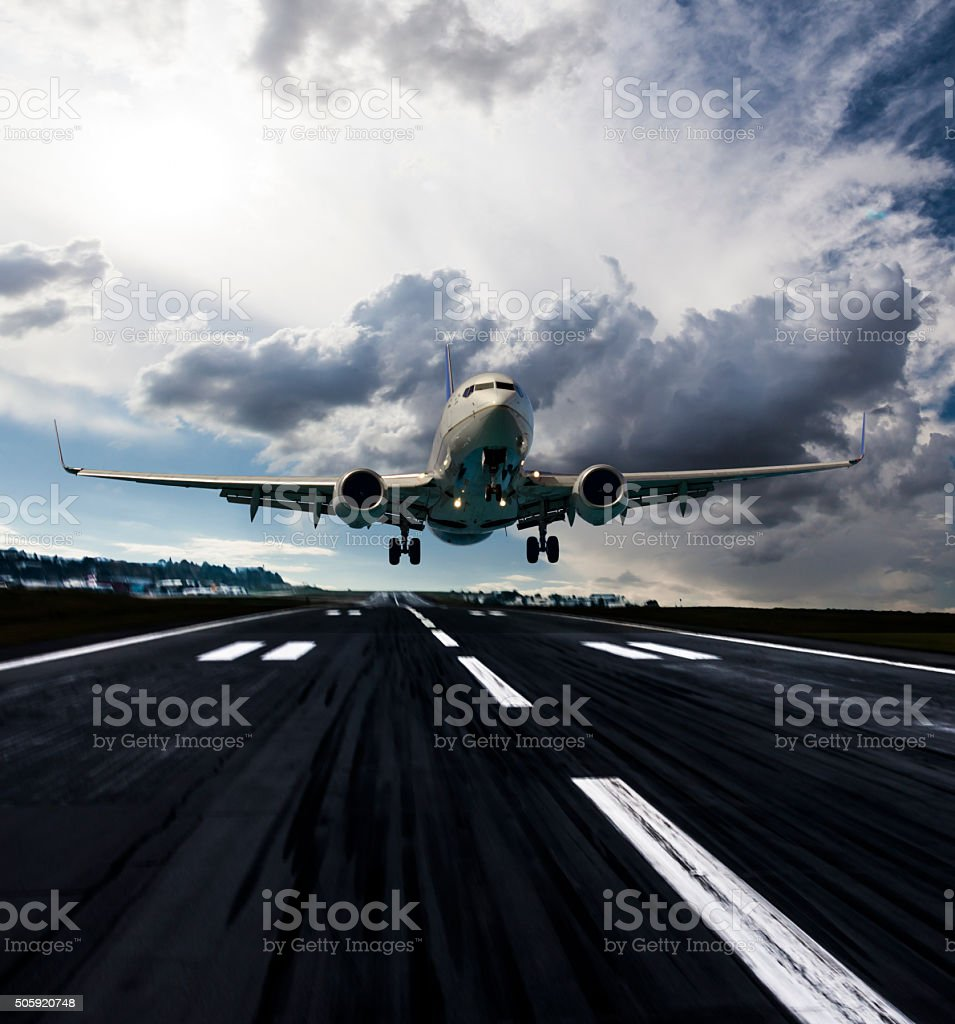 Passenger airplane landing at dusk stock photo