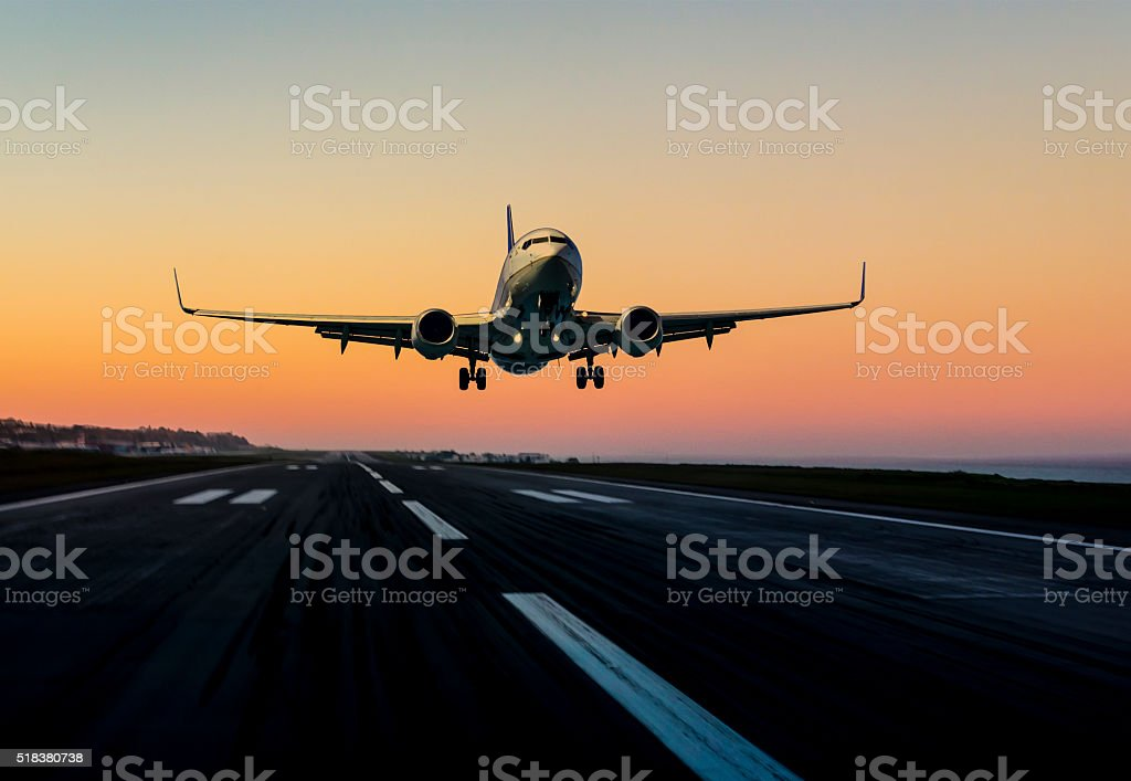 Passenger airplane landing at sunset stock photo