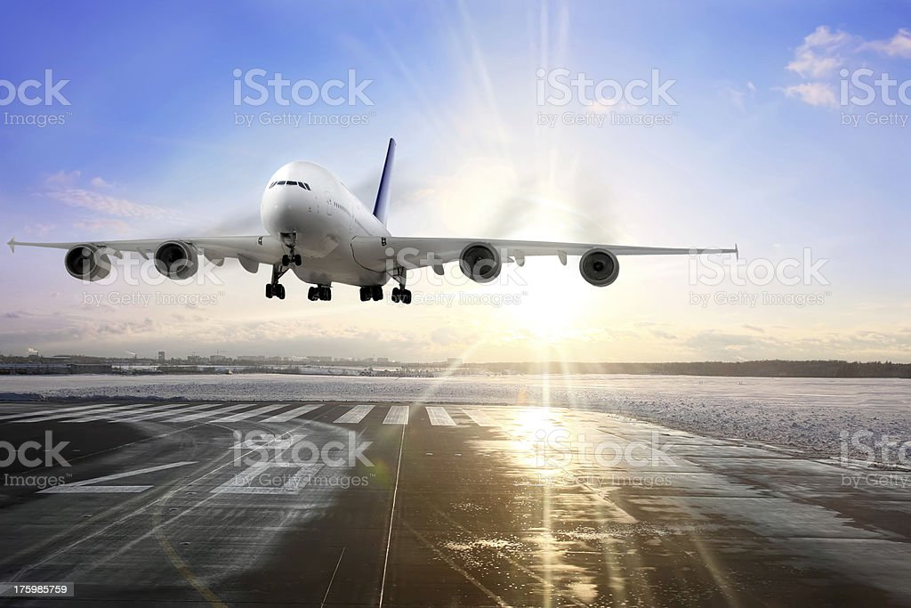 Passenger airplane landing on runway stock photo