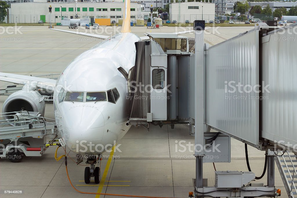 Passenger boarding bridge attached parked airplane stock photo