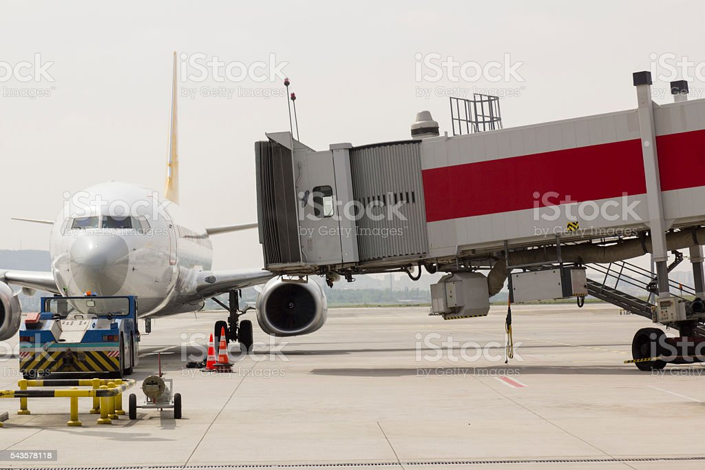 passenger boarding bridge connected to airplane at airport stock photo