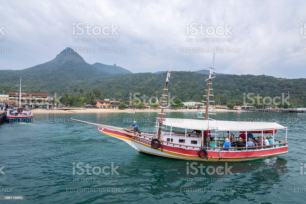 Passenger boat arriving at tropical resort stock photo