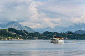 Passenger boat in front of snow covered Alps mountains peaks