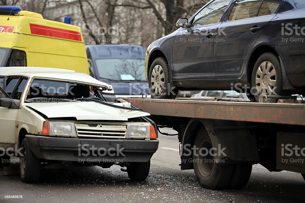 passenger car and a tow truck stock photo