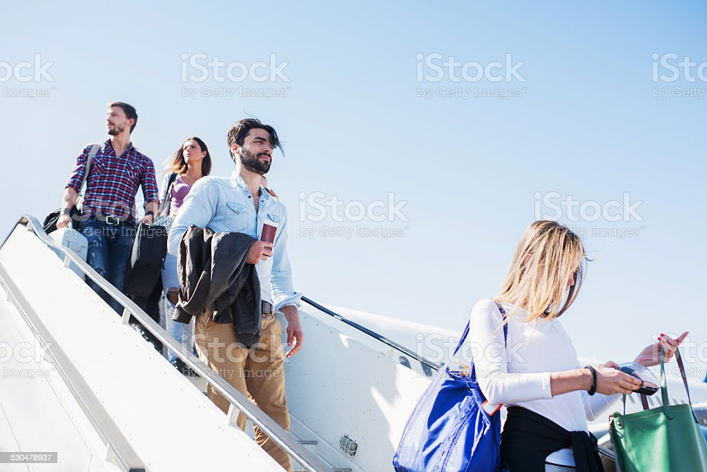 Passenger getting out of the plane. stock photo