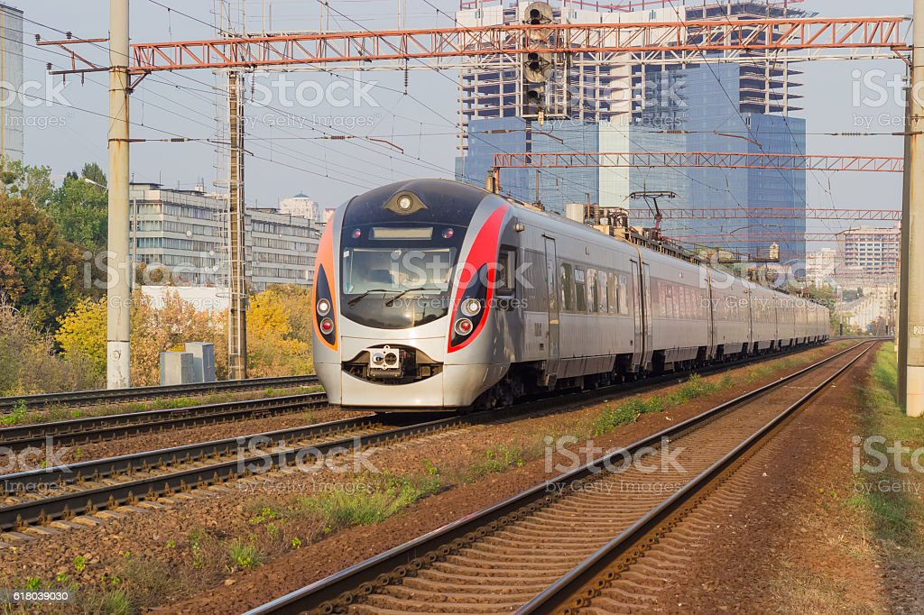Passenger inter-city train on the background of urban developmen stock photo
