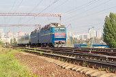 Passenger inter-city train on the background of urban developmen