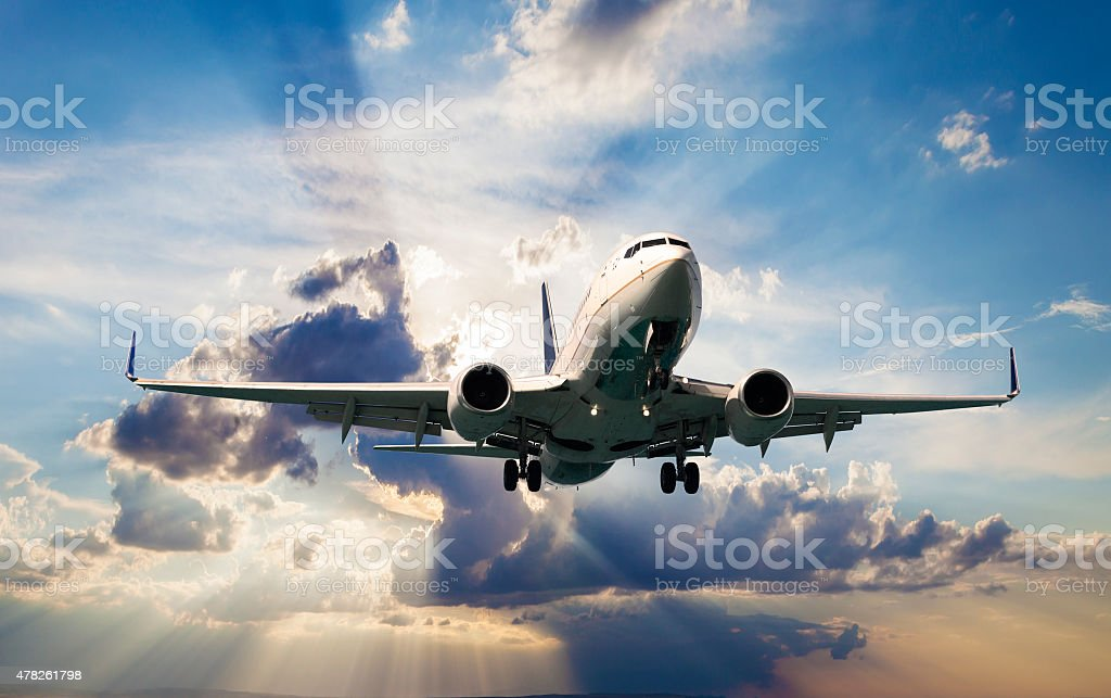 Passenger jet airplane over clouds stock photo