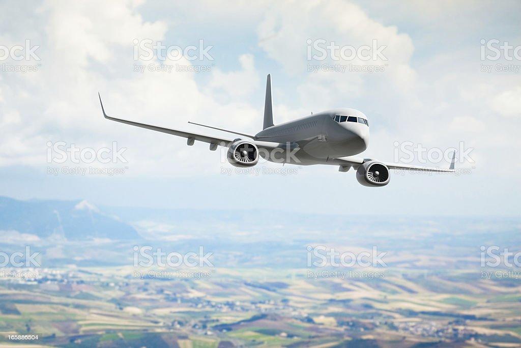 Passenger jet flying over fields stock photo
