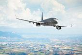 Passenger jet flying over fields